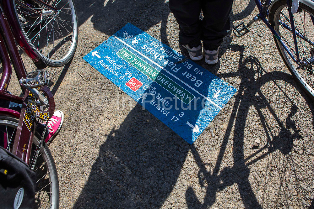 Cyclists stands next to a brand new public pathway signage on the Two Tunnels Greenway route showing directions to Midford, Radstock, Bath and Bristol in Somerset, England, United Kingdom.  The 13-mile route has been restored to provide a fantastic walking and cycling link between Central Bath, Midford, Monkton Combe and beyond and has involved the restoration of two disused railway tunnels. This development was started by a local community group and is part of the Sustrans lottery-funded project, Connect 2 Cycling Network.