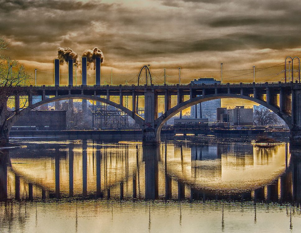 The Third Avenue Bridge (originally known as the St. Anthony Falls Bridge). This is a landmark structure of in Minneapolis, Minnesota. It carries road traffic across the Mississippi River and right over the upper fringes of Saint Anthony Falls. The multi-arched bridge meets with Third Avenue in downtown Minneapolis at its south end, but curves as it crosses the river, and connects with Central Avenue on its north end. The shallow  curve in the bridge was built to avoid fractures in the limestone bedrock that supports the bridge piers.<br /> <br /> Much of the design work was done by Minneapolis city engineer Frederick W. Cappelen, who was responsible for a number of other local bridges and structures. Beyond the bridge you see a high industrial area setting the mood for my approach to this shot.