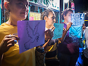 """06 JULY 2015 - BANGKOK, THAILAND: Women stand in support of 14 Thai university students arrested two weeks ago for violating orders banning political assembly in Thailand. More than 100 people gathered at Thammasat University in Bangkok Monday to show support for the students. They face criminal trial in military courts. The students' supporters are putting up """"Post It"""" notes around Bangkok and college campuses up country calling for the students' release.      PHOTO BY JACK KURTZ"""