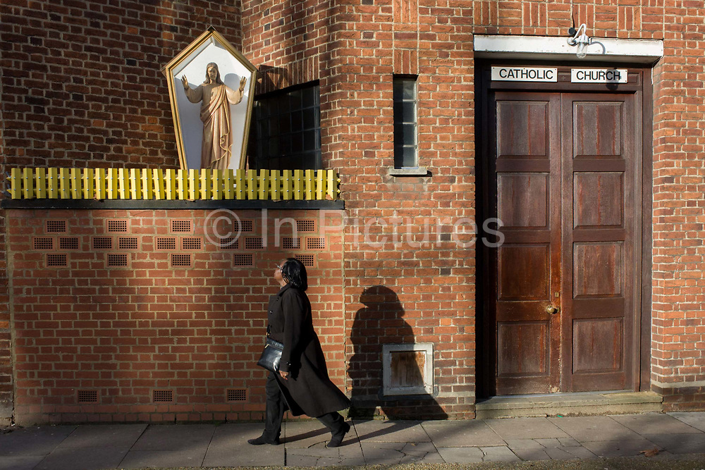 A local woman walks past an effigy of Jesus Christ encased in a shrine box outside a Catholic church in Camberwell, south London. The lady passes beneath the dominating figure that stands above the pavement. Encased in a glass-sided box and behind what resembles yellow garden fencing, the Christian idol stands with outstretched arms, a traditional figure for Catholics to practice idolatry. The church walls are constructed from red brick, in a style much-seen in industrial buildings.