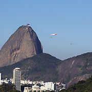 A airline jet flies past the summit of Sugar Loaf Mountain, one of the iconic locations with breathtaking views of Rio de Janeiro, Brazil. 22nd July 2010. Photo Tim Clayton..