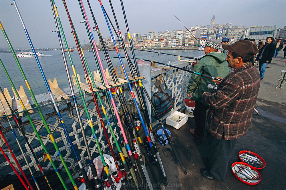 Fishermen catching istavrit (horse mackerel) line the Galata Bridge over the Bosphorus, the strait between the Black and Aegean seas. Located on a narrow isthmus between two bodies of water, the Turkish city of Istanbul (formerly known as Constantinople and, before that, Byzantium) long dominated the trade between Europe and Asia. The Galata District in the background, a hub for both entertainment and finance, is on the European side of the Bosphorus, both geographically and culturally. Hungry Planet: What the World Eats (p. 255). This image is featured alongside the Çelik family images in Hungry Planet: What the World Eats.