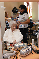 Elderly woman having her hair styled in the hairdressers,