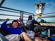 22 JANUARY 2019 - PHRA PRADAENG, SAMUT PRAKAN, THAILAND:  Workers in the back of a pickup truck on a motorcycle and vehicle ferry across the Chao Phraya River in Phra Pradaeng. The use of vehicle ferries across the river has gone down as the government has built bridges to connect communities on both sides of the river. The Phra Pradaeng ferries are the busiest ferries in the Bangkok metropolitan area. Since the BTS Skytrain now stops a few kilometers from the ferry, the number of commuters going into Bangkok that use the ferry has increased.      PHOTO BY JACK KURTZ