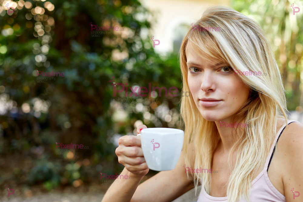 Cheerful young woman with long blond hair in light summer top holding in hand small cup with tea or coffee and looking at camera smiling on blurred background