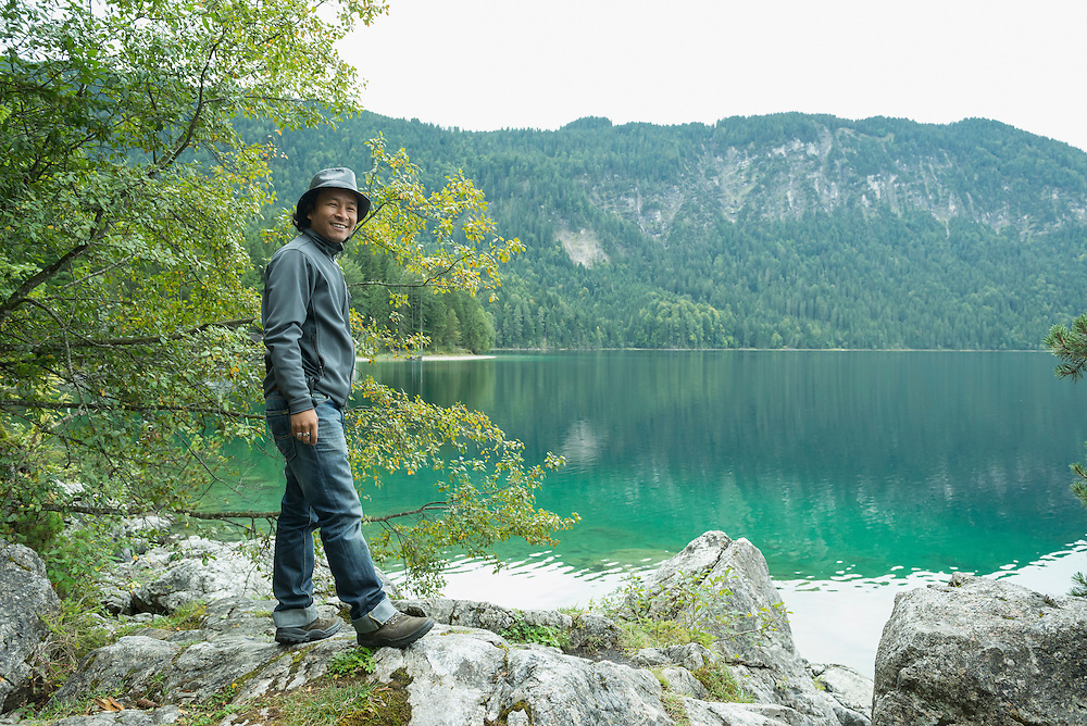 Tourist standing on rock at Eibsee lake, Bavaria, Germany