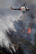 A helicopter makes a water drop onto a wildfire, Friday May 31, 2013, near Castiac, California. Fourteen aircraft and more than 550 firefighter were deployed in a ground and air campaign against a brush fire that has blackened about 1,500 acres in sparsely populated San Francisquito Canyon in the Angeles National Forest northeast of Santa Clarita. The Powerhouse Fire, which broke out Thursday afternoon, was about 15 percent contained. The estimated date of full containment is Wednesday, June 5. (Photo by Ringo Chiu/PHOTOFORMULA.com)