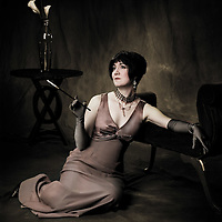 Victorian or Jazz era Lady, sitting by fainting couch with a cigarette holder