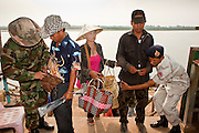08 APRIL 2010 - NAKHON PHANOM, THAILAND: Thai Border Police search Laotian citizens entering Thailand after crossing the Mekong River to shop in the market in That Phanom. One police officer that it was easier for criminals, mostly drug runners and immigrant smugglers, to sneak into Thailand because they could just walk across the river. The region is in the midst of a record setting drought and the Mekong River is at its lowest point in nearly 50 years, setting up an environmental disaster the region has never seen before. Many of the people who live along the river farm and fish. They claim their crops yields are greatly reduced and that many days they return from fishing with empty nets. The river is so shallow now that fisherman who used to go out in boats now work from the banks and sandbars on foot or wade into the river. In addition to low river levels the Isan region of Thailand is also in the midst of a record drought and heat wave. Farmers have been encouraged to switch from rice to less water intensive crops and to expect lower yields. Farmers here rely more on rain fall than irrigation to water their crops.       PHOTO BY JACK KURTZ