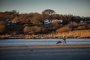 A man walks his dog on the beach at the entracne to the Narrow River, Narragansett, Rhode Island.