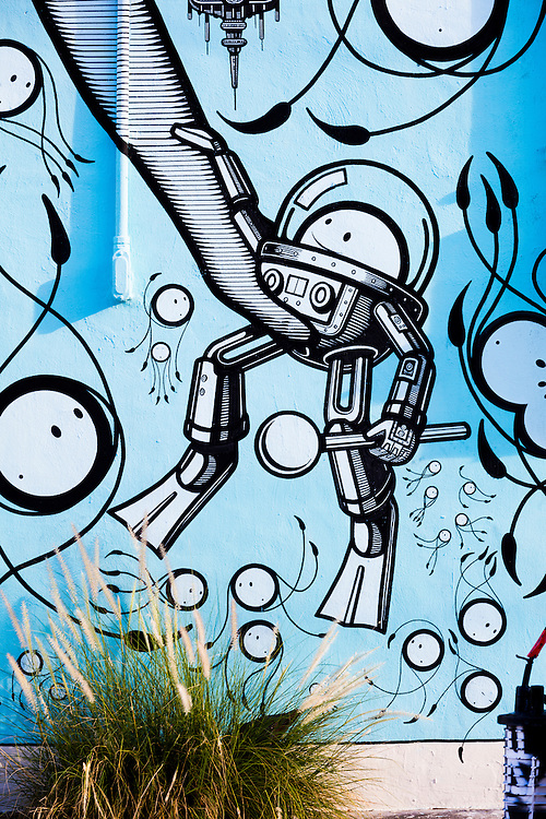 """Detail of a whimsical mural painted by """"The London Police"""" in Miami's Wynwood district depicting science fiction-like, deep sea diving suits for little, round-faced creatures."""