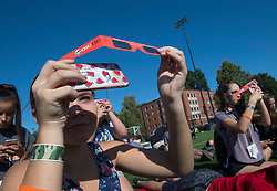 August 21, 2017 - Corvallis, Oregon, U.S - Girls use their  cell phones to photograph the sun as they gather with others to watch the total solar eclipse as seen from the State University campus in Corvallis. The eclipse is the first coast-to-coast solar eclipse in almost 100 years and will pass across the U.S. at 2,000 mph. Millions of people are staking out prime viewing spots to watch, especially along the path of totality — the line of shadow created when the sun is completely obscured. The path of totality, darkness will last no more than a few minutes. (Credit Image: © Robin Loznak via ZUMA Wire)