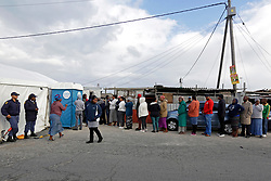 Wednesday 8th May 2019.<br /> Monwabisi Park, Harare,<br /> Khayelitsha, Cape Town, <br /> Western Cape, <br /> South Africa.<br /> <br /> SOUTH AFRICAN GENERAL ELECTIONS 2019!<br /> <br /> SOUTH AFRICAN PROVINCIAL AND NATIONAL ELECTIONS 2019! <br /> <br /> Voters stand under a lamp pole with some political party posters on it outside the voting station as they queue together waiting to cast their vote at Monwabisi Park, Harare in Khayelitsha near Cape Town, Western Cape, South Africa.<br /> <br /> Registered South African Voters head to the various IEC (Independent Electoral Commission) Voting Stations where they are registered to vote as they cast their votes and take part in voting and other activities on Voting Day 8th May 2019 during the South African General Elections 2019. Voters from across the nation stood in queue's along with many others to vote in the Provincial and National Elections being held in South Africa on Wednesday 8th May 2019.   <br />  <br /> Copyright © Mark Wessels. All Rights Reserved. No Usage Without Permission.<br /> <br /> PICTURE: MARK WESSELS. 08/05/2019.<br /> +27 (0)61 547 2729.<br /> mark@sevenbang.com<br /> studioseven@mweb.co.za<br /> www.markwesselsphoto.com
