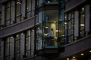 A businessman stands up from his desk in his office in late afternoon, in the City of London.