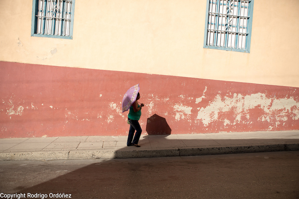 A woman uses an umbrella to shelter herself from the strong midday sun in the streets of Santiago de Cuba, Cuba, on December 27, 2014.