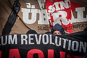 """01/05/2015 – Berlin, Germany: A member of an anarchist group looks between banners during the """"Revolutionary 1st of May Demonstrations"""" in Kreuzberg. The International Workers Day is a celebration of laborers and the working classes that is promoted by the international labor movement, anarchists, socialists, and communists and occurs every year on May Day. (Eduardo Leal)"""