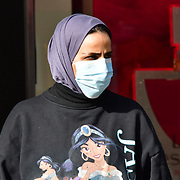 A Asian women wearing a mask cross the street during Coronavirus - Pandemic hit Oxford Street many shops closure a few open but empty on 21 March 2020, UK.