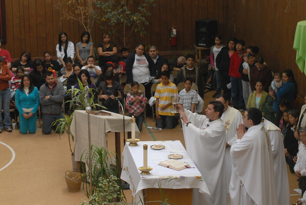 Father Franco Liporace leads parishioners at St. Francis of Assisi Catholic Church in worship during a weekly mass in the church gymnasium.