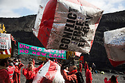 Hundreds of environmental activists stopping the open cast coal mine Ffos-y-Fran near Merthyr Tydfil, Wales from operating May 3rd 2016. The iconic Red Line inflateable cobble stones fly through the air in the mine. The activists from Reclaim the Power wants the mine shut down and a moratorium on all future open coal mining in Wales. The group Reclaim the Power had set up camp near by and had over three days prepared the action and up to 300 activists all dressed in red went into the mine in the early morning. The activist were plit in three groups and carried various props signifying the red line in the sand, initially drawn in Paris at the COP21. The mine is one of the largest open cast coal mines in the UK and is run by Miller Argent who have to date extracted 5million tons of coal. The activists entered the mine unchallenged by any security or police and the protest went on peacefully till mid afternoon with no arrests made.  Open coal mining is hugely damaging to the local environment and  contributing to global climate change.