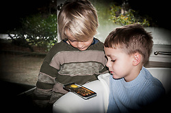 Two boys using smart phone at home