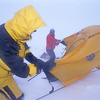 BAFFIN ISLAND, NUNAVUT, CANADA. Alex Lowe & Mark Synott (MR) set up tent in a blizzard north of the Arctic Circle, near Sam Ford Fjord, en route to climbing expedition north of Clyde River.