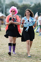 © Licensed to London News Pictures. 06/09/2014. Isle of Wight, UK. Festival goers at Bestival 2014 Day 3 Saturday wearing disco fancy dress walking in the morning sunshine.  Today is the festival's Fancy Dress Day - this year the theme is Desert Island Disco.  Festival goers spend the morning readying their costumes before the judging of the competition at 2pm.  This weekend's headliners include Chic featuring Nile Rodgers, Foals and Outcast.   Bestival is a four-day music festival held at the Robin Hill country park on the Isle of Wight, England. It has been held annually in late summer since 2004.    Photo credit : Richard Isaac/LNP