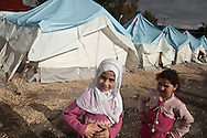 Rahuf and Raida, 10 years old, enjoy a break from the rain in Yayladagi refugee camp for Syrians in southern Turkey. 12/21/2012 Bradley Secker for the Washington Post