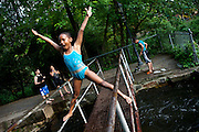 """BETHLEHEM, PA – MAY 27, 2011: Niyanda Magagi, 9, does a stunt over the water at the Lehigh Canal on a Saturday afternoon at Sand Island in Bethlehem, Pennsylvania. Commonly known as """"The Box,"""" the water at Sand Island is one of several well known recreational spaces for the burgeoning Latino community in the town of Bethlehem.<br /> <br /> As the population of second and third generation Hispanics increases dramatically in the United States, a new boldness can be sensed among Latinos in America, stretching far beyond the southern border states. Demographers in Pennsylvania say the towns of Bethlehem, Allentown and Reading are set to become majority-minority cities, where Hispanics comprise a bigger portion of the population than whites. As this minority population increases dramatically in the region, Latinos are inching closer to their own realization of the American Dream, while gradually shifting the physical and cultural landscapes of their communities."""