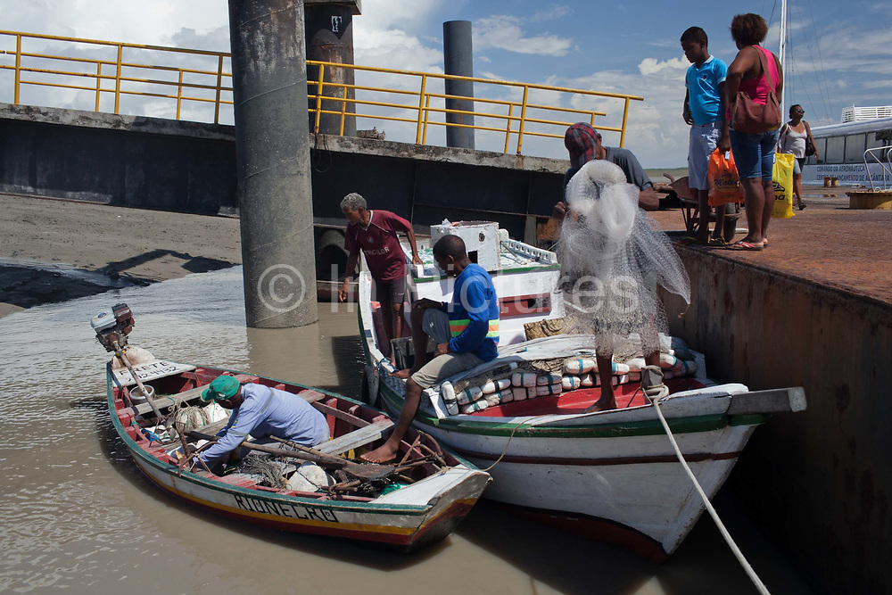 People boarding a fishing boat in Alcantara on 27th May 2014, Maranhao, Brazil. It is an island off the north east coast of Brazil close to Sao Luis, state capital of, and is one of the largest Quilombos in Brazil, which are communities that were originally set up by escaped or freed slaves during the colonial period.