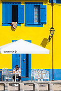Man outside cafe of brightly coloured blue and yellow facade in Cais dos Botiroes harbour side by marina at Aveiro, Portugal