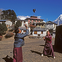 Young Buddhist monks play with a makeshift ball at the old Tengboche Monastery, below Mount Ama Dablam in Nepal's Khumbu region. (After this picture was taken in 1979, the monastery burned down in 1989 and was rebuilt.)  The summit of Mount Everest is just left of the central pagoda roof.