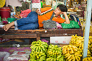 """26 SEPTEMBER 2012 - BANGKOK, THAILAND: A wholesale banana vendor checks his smart phone while he relaxes in Khlong Toey Market in Bangkok. Klong Toey (also called Khlong Toei) Market is one of the largest """"wet markets"""" in Thailand. The market is located in the midst of one of Bangkok's largest slum areas and close to the city's original deep water port. Thousands of people live in the neighboring slum area. Thousands more shop in the sprawling market for fresh fruits and vegetables as well meat, fish and poultry.     PHOTO BY JACK KURTZ"""