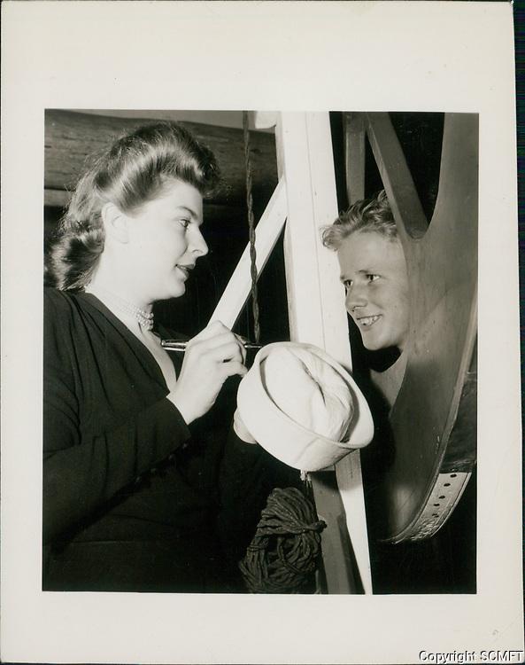 1944 A hostess signs a sailor's hat after he won the War Bond raffle