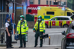 """© Licensed to London News Pictures. 28/06/2021. London, UK. London Ambulance Service (LAS) paramedics talk to a police officer inside a cordon. One hundred firefighters tackled a fire near Elephant and Castle railway station in southeast London. London Fire Brigade (LFB) said three commercial units in railway arches were """"completely alight"""", in addition to six cars and a telephone box. Photo credit: Peter Manning/LNP"""