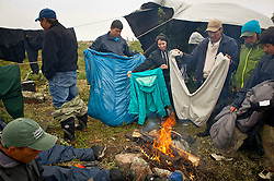 The small group of Dene First Nation try to dry off their soaked sleeping bags and clothes after days of rain while paddling down the Thelon river In the middle of the largest and most remote game sanctuary in North America, in the Northwest Territories, just south of the Arctic Circle. Its fate now hangs in the balance, protected on paper, but with little management, no money, and no voice for the Dene, its most ardent advocate for protection, while mining (for diamonds, gold, and uranium) threats, buoyed by recent prices, loom.  Dene youth have rarely been deep into the Thelon, yet the caribou is still their life blood, reverentially important.  These Dene are amongst the last hunter/gatherers in the Northern Hemisphere.   (Photo by Ami vitale)
