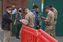 © Licensed to London News Pictures. 29/05/2021. Bolton,UK. Members of the public queue at a temporary Covid-19 vaccination centre at Eden Boys' school in Halliwell, Bolton. Bolton has the highest Covid-19 infection rate in the country as the Indian variant of Covid-19 continues to spread.  Photo credit: Ioannis Alexopoulos/LNP