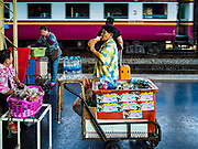 11 APRIL 2018 - BANGKOK, THAILAND: A vender drinks a soft drink while she waits for customers on a platform at Hua Lamphong train station in Bangkok. Songkran is the traditional Thai New Year and is one of the busiest travel periods of the year as Thais leave the capital and go back to their home provinces or resorts in tourist areas.      PHOTO BY JACK KURTZ