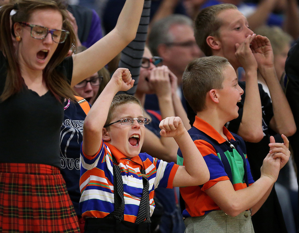Cross County fans, Leighton Nuttelman, middle, 9, and Camery Nielsen, left, and Colton Nuttelman, right, cheer on the Lady Cougars in the first set of Thursday's match against Red Cloud at Gibbon High School. Cross County defeated Red Cloud 25-16, 25-20, 25-27, 25-16. (Independent/Matt Dixon)