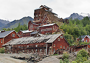 """Kennecott Concentration Mill rises 14 stories tall beneath Bonanza Ridge in the Wrangell Mountains, Alaska, USA. Kennecott Mines National Historic Landmark and nearby McCarthy lie within Wrangell-St. Elias National Park and Preserve, the largest National Park in the USA. Old mine buildings, artifacts, and colorful history attract summer visitors. Remote McCarthy is connected to Chitina via the McCarthy Road spur of the Edgerton Highway. At the east end of McCarthy Road, visitors must park their vehicle and walk across the footbridge to McCarthy. From McCarthy, a privately-operated shuttle takes visitors 5 miles to Kennecott. After copper was discovered between the Kennicott Glacier and McCarthy Creek in 1900, the Kennecott town, mines, and Kennecott Mining Company were created and named after the adjacent glacier. Kennicott Glacier and River had previously been named after Robert Kennicott, a naturalist who explored in Alaska in the mid-1800s. The corporation and town stuck with a mistaken spelling of """"Kennecott"""" with an e (instead of """"Kennicott"""" with an i). Partly because alcoholic beverages and prostitution were forbidden in the company town of Kennecott, the neighboring town of McCarthy grew quickly to provide a bar, brothel, gymnasium, hospital, and school. The Copper River and Northwestern Railway reached McCarthy in 1911 to haul over 200 million dollars worth of ore 196 miles to the port of Cordova on Prince William Sound. By 1938, the worlds richest concentration of copper ore was mostly gone, the town was mostly abandoned, and railroad service ended. Not until the 1970s did the area began to draw young people for adventure and the big money of the Trans Alaska Pipeline project. Declaration of Wrangell-St. Elias National Park in 1980 drew adventurous tourists who helped revive McCarthy with demand for needed services. Wrangell-St. Elias National Park and Preserve is honored by UNESCO as a World Heritage Site."""