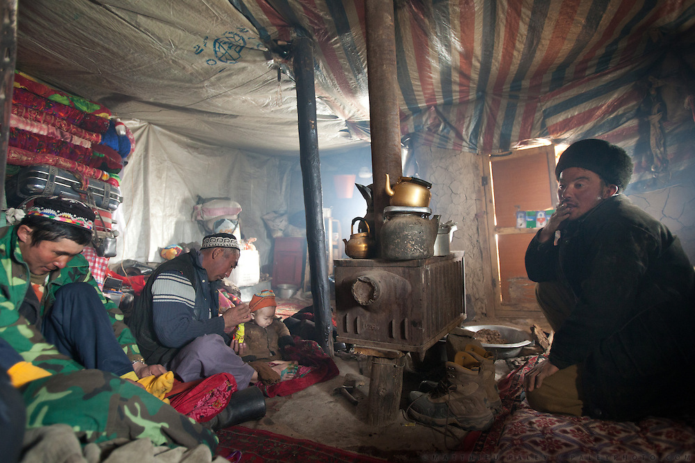 Having tea and sitting around the winter home of Sher Ali. At the Andemin camp...Trekking through the high altitude plateau of the Little Pamir mountains, where the Afghan Kyrgyz community live all year, on the borders of China, Tajikistan and Pakistan.