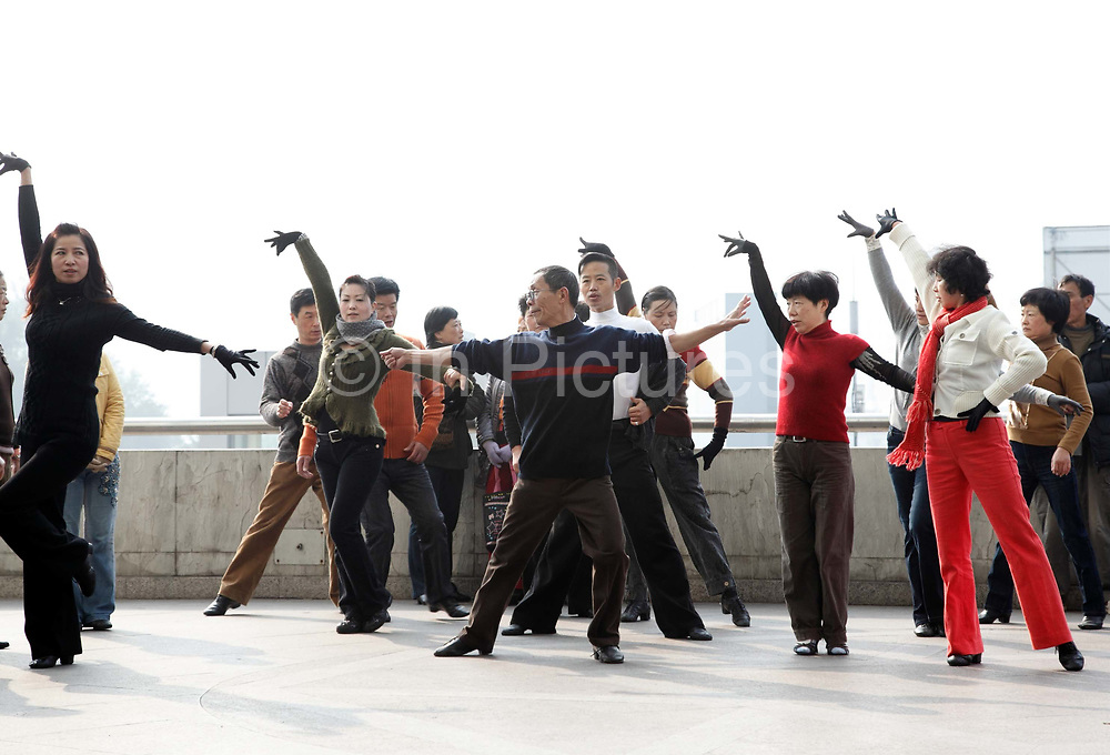 """Enthusiasts practice their Cha-Cha moves on a sidewalk in Shanghai, China on 22 November 2009. Once frowned upon by the communist masses as """"bourgeoisie"""", dancing has become a popular pastime for many middle aged and elderly people in China not only as good physical exercise, but an opportunity to gather and meet people."""