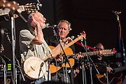 Pete Seeger, left, honorary chair of the concert, cups his ear to get the audience to sing louder. On his right is Tom Chapin.
