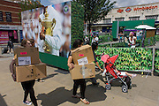 Day 2 of the annual lawn tennis championships women carry boxes and spectators mingle with locals near a large champions trophy billboard, outside the mainline and underground (subway) station in the south London suburb. The Wimbledon Championships, the oldest tennis tournament in the world, have been held at the nearby All England Club since 1877.