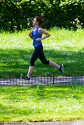 A woman runs through the dappled sunlight on a perfect spring day in Regents Park. London, May 04 2018.