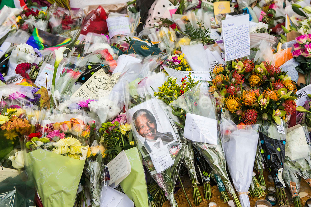 Floral tributes laid around the base of the statue of Nelson Mandela in Parliament Square, London, UK after his death. The statue is a bronze sculpture of former President of South Africa and anti-apartheid activist Nelson Mandela by the artist Ian Walters.