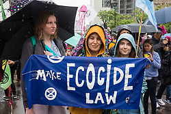 London, UK. 19 July, 2019. Climate activists from Extinction Rebellion with a 'Make Ecocide Law' banner arrive in Parliament Square on a march from their camp at Waterloo Millennium Green on the fifth day of their 'Summer uprising' to call on local and central government to take urgent steps to address the climate emergency.