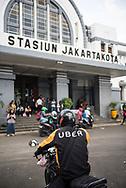 Jakarta, Indonesia - July 10, 2017: An Uber motor driver waits outside the Jakarta Kota railway station in Jakarta, Indonesia.