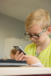Close-up of a schoolboy using smart phone in classroom, Munich, Bavaria, Germany