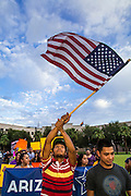 15 AUGUST 2012 - PHOENIX, AZ:  A man waves an American flag while he marches to the Arizona State Capitol. About 200 people, mostly DREAM Act  (an acronym for Development, Relief, and Education for Alien Minors) students and their family members, marched on the Arizona State Capitol in Phoenix Wednesday after Arizona Governor Jan Brewer said the state of Arizona will not give DREAM Act students any state services, including driver's licenses or tuition breaks on state universities and schools. Brewer has been a critic of President Obama's plan to defer deportations of certain undocumented young people.  PHOTO BY JACK KURTZ