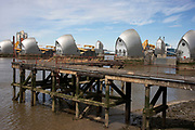 An old wooden jetty contrasts old with new against the Thames Barrier in London, United Kingdom. This is the flood defences for the capital. On high tides and when water levels are high, the barrier raises to hold back the water level.